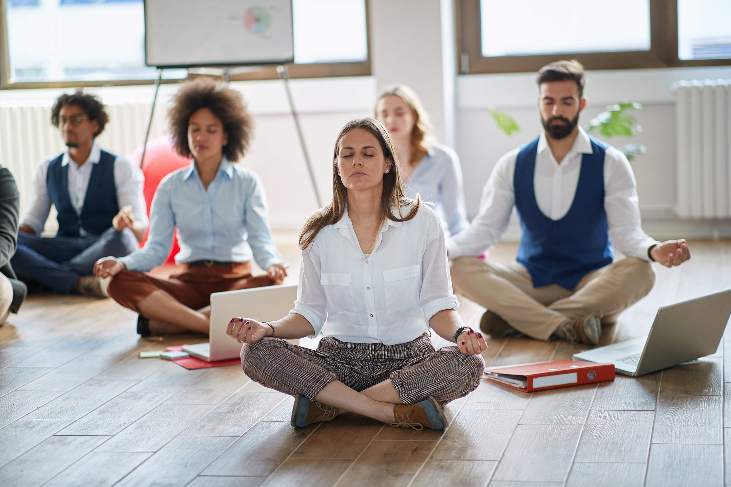 Businesswoman meditating at work.group of business coworkers meditating together.